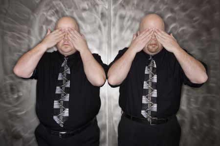 kinship: Caucasian bald mid adult identical twin men standing with hands covering eyes.