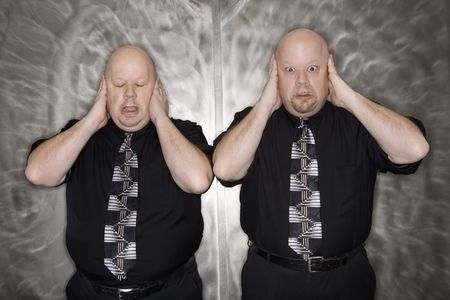 Caucasian bald mid adult identical twin men standing with hands covering ears making facial expression. photo