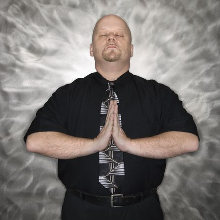 Caucasian bald mid adult men standing with hands together and eyes closed in a meditative position. photo