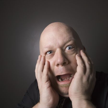 only mid adult men: Caucasian mid adult bald man with hands to face making scared facial expression.