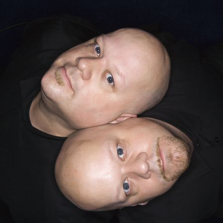 kinship: Aeriel view of Caucasian bald identical twin men sitting back to back and looking up at viewer.