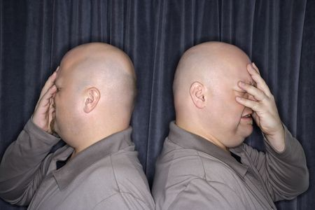 kinship: Profile of Caucasian bald identical twin men standing back to back and grimicing with hands to head.