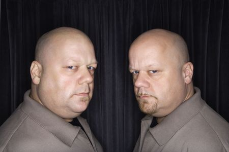 alike: Caucasian bald mid adult identical twin men looking sternly at viewer.