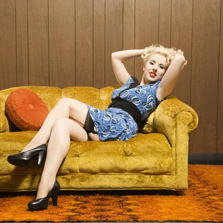 Attractive Caucasian woman laying on retro couch holding hair up. photo