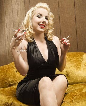 Attractive Caucasian woman holding a martini and cigarette. Stock Photo - 2440671