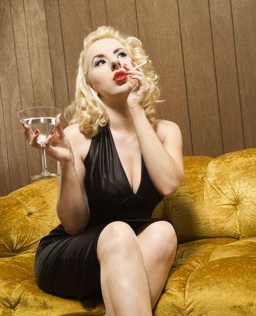 retro woman: Attractive Caucasian woman holding a martini and cigarette.