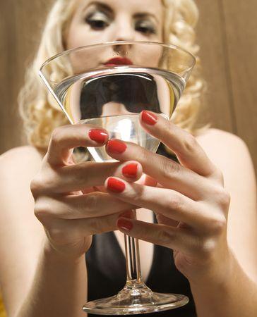 retro woman: Attractive blond Caucasian woman holding a martini glass.