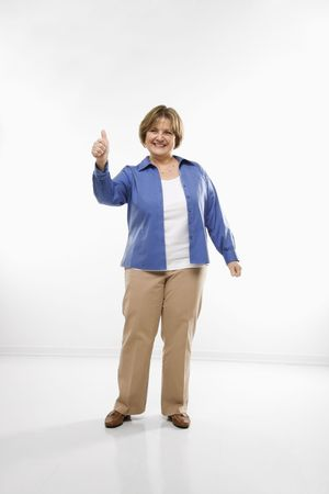 optimisim: Caucasian middle aged woman giving  thumbs up and smiling at viewer.
