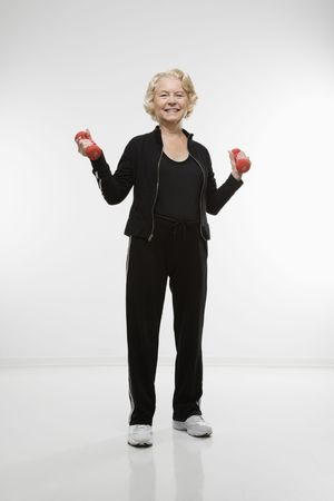70s adult: Caucasian senior woman holding dumbbells smiling at viewer. Stock Photo