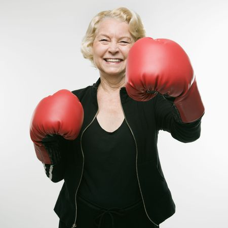 woman boxing gloves: Caucasian senior woman wearing boxing gloves throwing punch.