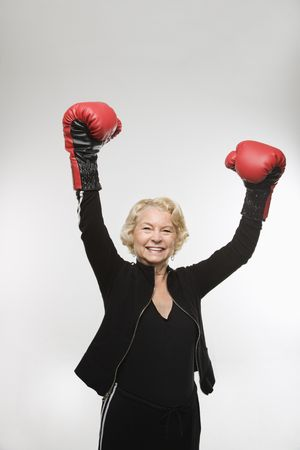 only mature women: Caucasian senior woman wearing boxing gloves raised in the air.