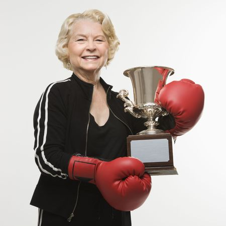 Caucasian senior woman wearing boxing gloves holding trophy. photo