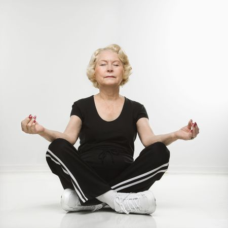 adults only: Caucasian senior woman sitting in yoga position on floor meditating.