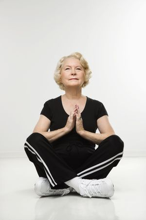 70s adult: Caucasian senior woman sitting in yoga position on floor meditating.