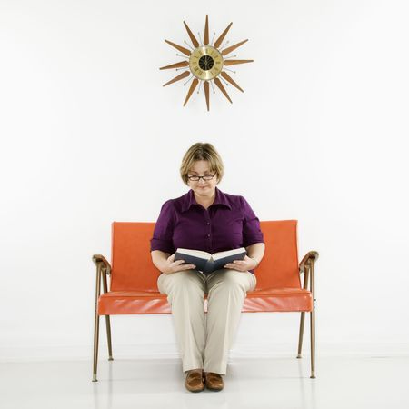 educating: Caucasian middle aged woman sitting reading book.