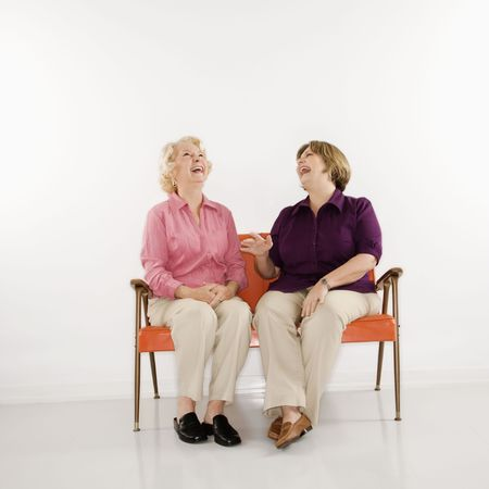 Caucasian middle aged woman and senior woman sitting and laughing. photo
