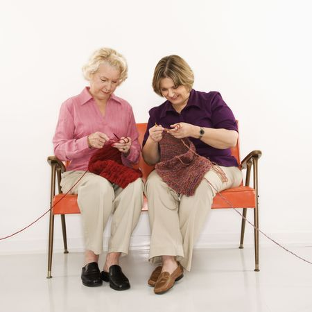 Caucasian middle aged woman and senior woman sitting and knitting. photo