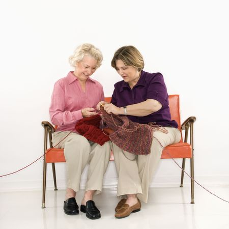retro woman: Caucasian middle aged woman and senior woman sitting and knitting.