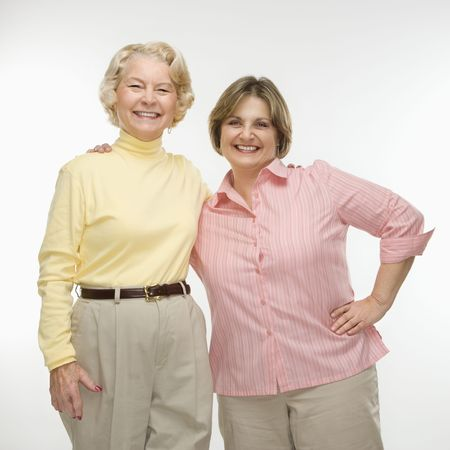 middle aged woman smiling: Caucasian senior woman and middle aged woman smiling with arms around each other.