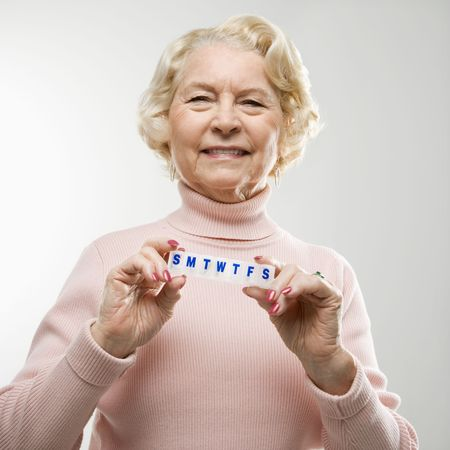 pill box: Caucasian senior woman holding pill box and smiling at viewer.