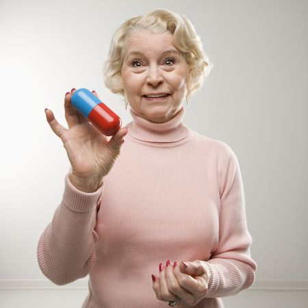 oversized: Caucasian senior woman holding oversized pill at viewer.
