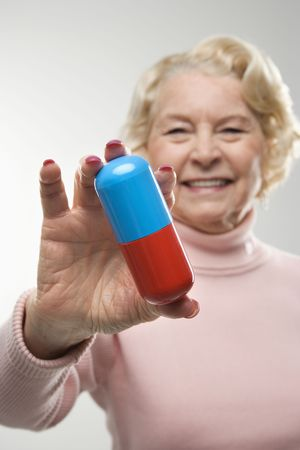 Caucasian senior woman holding oversized pill at viewer. photo