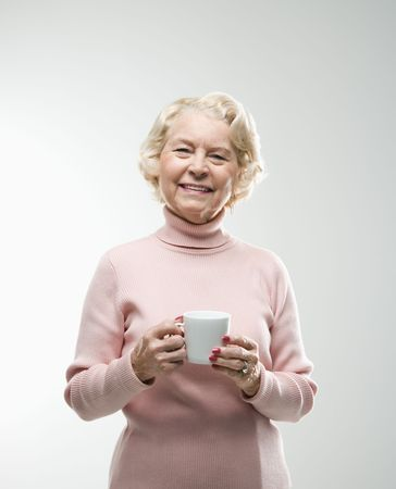 Caucasian senior woman holding coffee cup smiling at viewer. photo