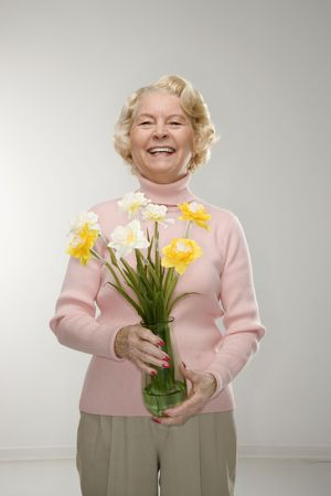 Caucasian senior woman holding bouquet and smiling at viewer. photo