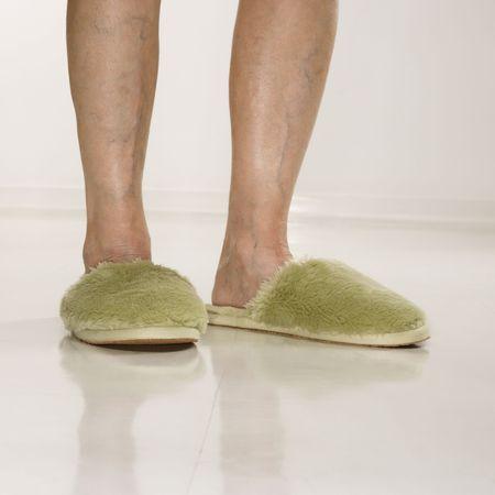 Caucasian senior female feet wearing green bedroom slippers. photo