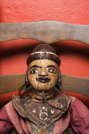 Close up of wooden puppet sitting on chair. photo