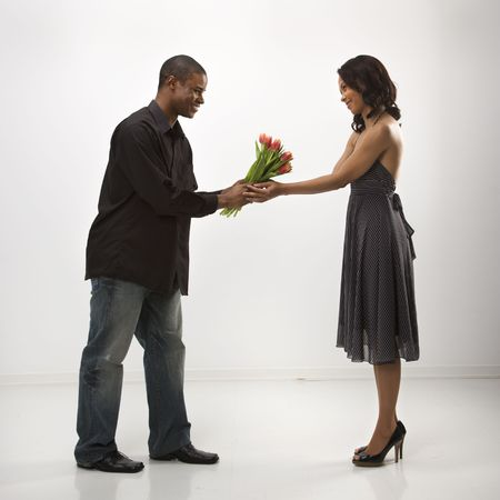African American mid adult man giving woman bouquet of flowers. photo