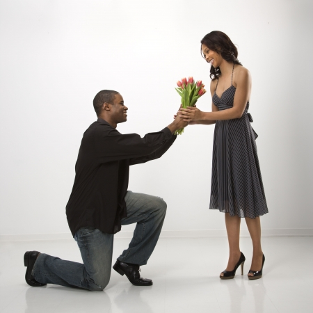 African American mid adult man on knees giving woman bouquet of flowers. photo