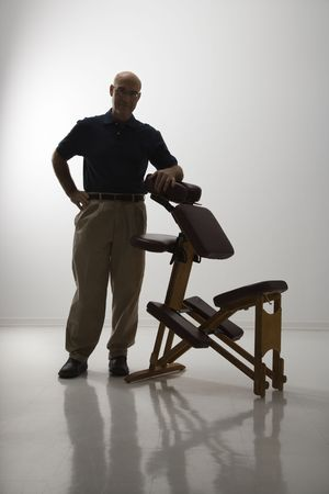elbow chair: Silhouette of Caucasian middle-aged male massage therapist standing with elbow on massage chair.