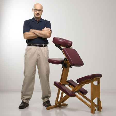 Caucasian middle-aged male massage therapist standing with arms crossed beside massage chair. photo