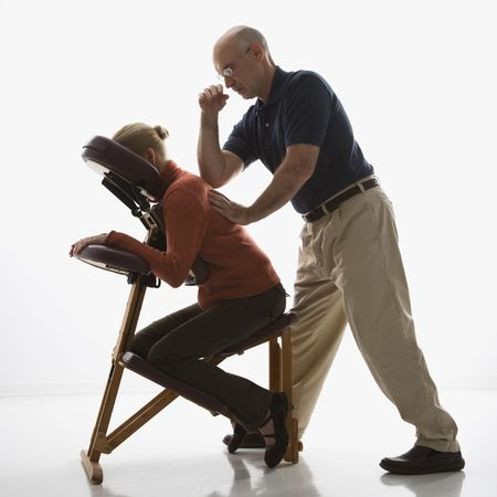 Caucasian middle-aged male massage therapist massaging back of Caucasian middle-aged woman sitting in massage chair with his elbow.