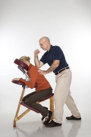 elbow chair: Caucasian middle-aged male massage therapist massaging back of Caucasian middle-aged woman sitting in massage chair with his elbow.