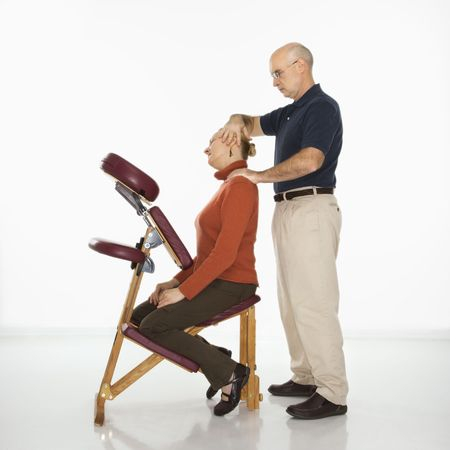 Caucasian middle-aged male massage therapist massaging neck of Caucasian middle-aged woman sitting in massage chair.  photo
