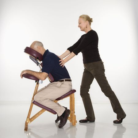 Caucasian middle-aged female massage therapist massaging back of Caucasian middle-aged man sitting in massage chair.  photo