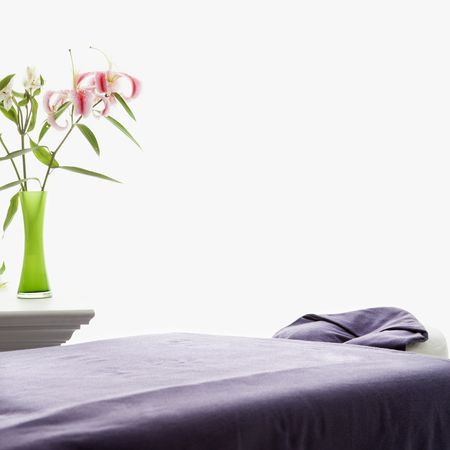 Spa scene of massage table with purple sheets and table with pink Easter lillies in green vase.