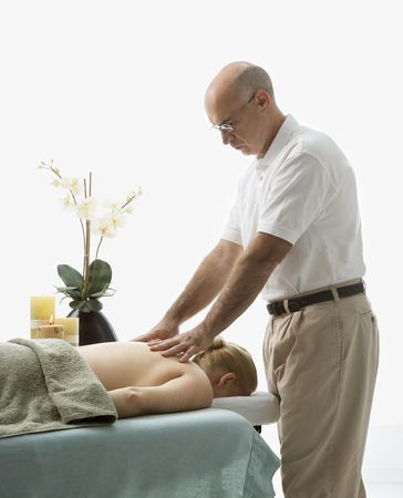 Caucasian middle-aged male massage therapist massaging back\ of Caucasian middle-aged woman lying on massage table.