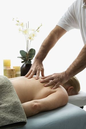 Caucasian middle-aged male massage therapist massaging back of Caucasian middle-aged woman lying on massage table.