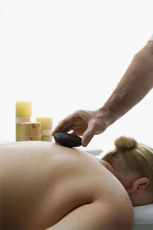 Caucasian middle-aged male massage therapist placing hot stone on back of Caucasian middle-aged woman lying on massage table. photo