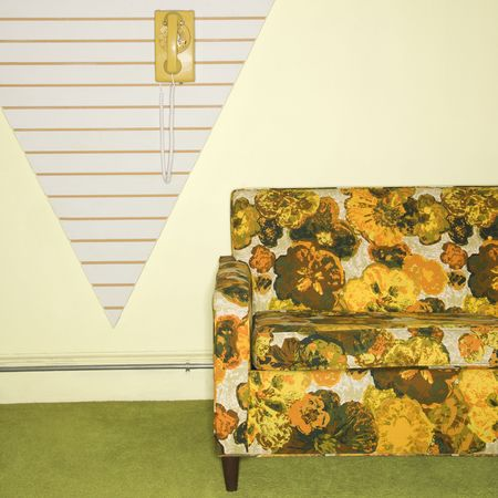 couches: Retro floral printed sofa with yellow rotary phone hanging on wall.