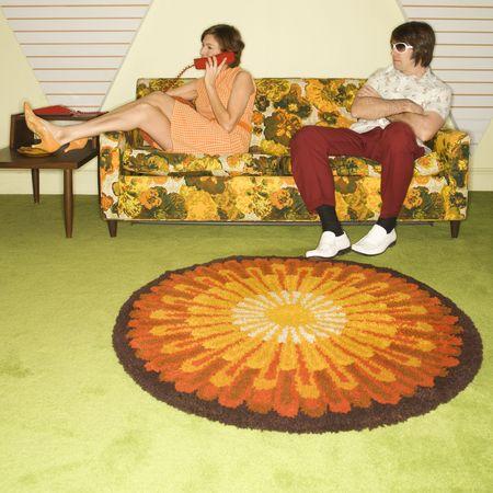 everyday scenes: Caucasica met� donna adulta sul telefono mentre caucasica met� uomo adulto di indossare occhiali da sole orologi da divano.  Archivio Fotografico