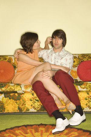 timidity: Pretty Caucasian mid-adult woman flirting with Caucasian mid-adult man sitting on colorful retro sofa. Stock Photo