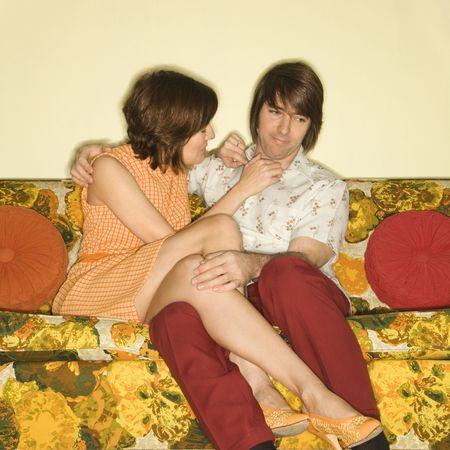 Pretty Caucasian mid-adult woman flirting with shy Caucasian mid-adult man sitting on colorful retro sofa. Stock Photo