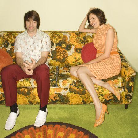 timidity: Pretty Caucasian mid-adult woman flirting with shy Caucasian mid-adult man sitting on colorful retro sofa. Stock Photo