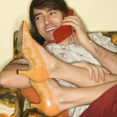 Caucasian mid-adult man talking on telephone with Caucasion mid-adult womans legs draped over lap. photo