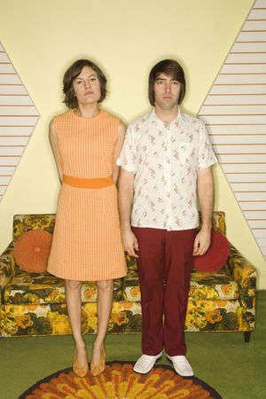 Caucasian retro couple standing in room decorated with vintage furniture. photo
