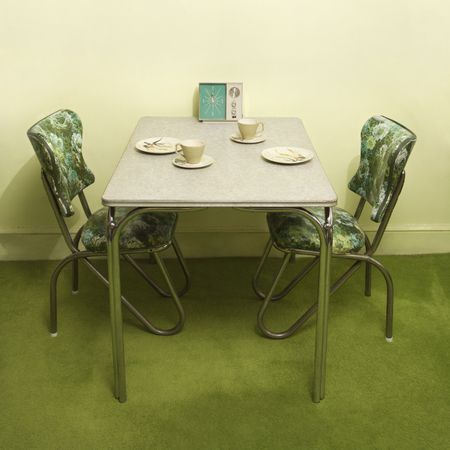 Retro 50s formica and chrome dinette set with green vinyl chairs.